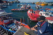 Harbor tour boat filling up with tourists, Port of Valparaiso, Chile