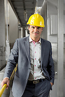 Portrait of confident young manager wearing hard hat in industry