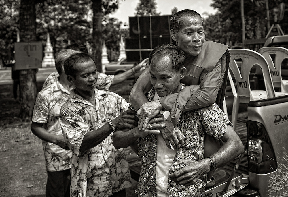 Thai men carry the head monk to the temple during Songkran in Nakhon Nayok, Thailand