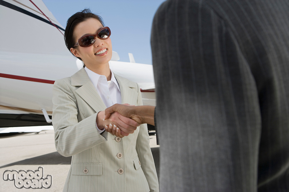 Two mid-adult businesswomen shaking hands in front of private plane.