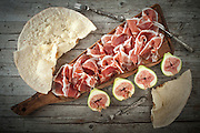 Fresh figs with ham and flat bread on wood table, overhead shot.