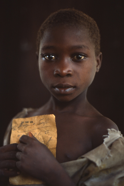 At a clinic a Tanzania girl waits for a medical check up holding her worn health card