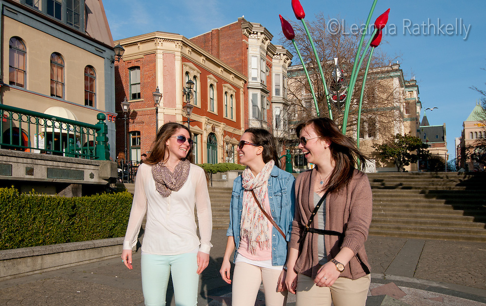 Three young women enjoy sightseeing near Bastion Square in downtown Victoria, BC Canada.