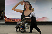 A mother pushes a child's buggy past a billboard ad featuring the face of a model advertising a perfume outside the retailer Debenhams on Oxford Street, on 16th April 2018, in London, England.