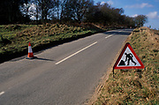 A753WF Roadworks red triangle sign with figure digging, quiet country road England