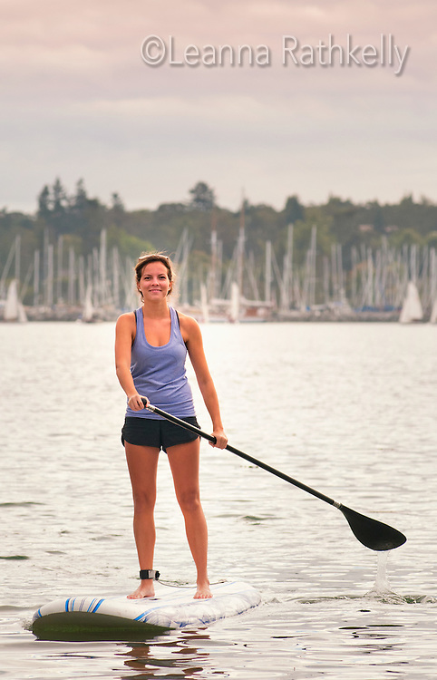 Taylor Kelly paddle boards in the calm ocean water of Cadboro Bay, Victoria, BC Canada
