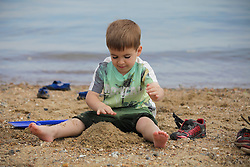 © Licensed to London News Pictures. 23/05/2015. St. Helens, UK. Joe (6), from Hampshire, fishing for crabs and enjoying the warm and sunny weather at The Duver beach in St. Helens on the Isle of Wight today, Friday 23rd May 2015. Today has been warm and sunny in the South of England. Photo credit : Rob Arnold/LNP