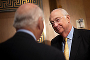 Former Sen. PHIL GRAMM, (R-TX) talks with Senator Ben Cardin (D-MD) before he is to testify at a Senate Finance Committee hearing on Budget Enforcement Mechanisms. In 1985 and 1987 Gramm spearheaded the Gramm-Rudman Acts which were a means of cutting the budget through across-the-board spending cuts if deficit-reduction targets were not met. Gramm is vice chairman of UBS Investment Bank.