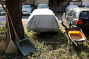 parked car with protective cover and garden tools