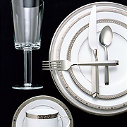 high end dishes and siverware on black from overhead