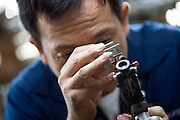 Kazuhito Komatsu, president of Komatsu Cutting Factory, looks through a loupe at a precious stone he is cutting and processing at his company in Kofu City, Yamanashi Prefecture, Japan on 16 Oct. 2012.   Photographer: Robert Gilhooly