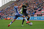 Brighton & Hove Albion defender Sebastien Pocognoli (12) is closed down by Wigan Athletic midfielder Michael Jacobs (17) during the EFL Sky Bet Championship match between Wigan Athletic and Brighton and Hove Albion at the DW Stadium, Wigan, England on 22 October 2016.