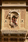 INDIA, RAJASTHAN girls in the carved window of her home in the ancient city of Jaisalmer, in the  Great Thar Desert