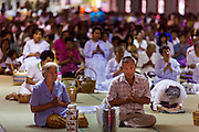 "12 JULY 2014 - PHRA PHUTTHABAT, SARABURI, THAILAND: People pray at the chanting service before the Tak Bat Dok Mai at Wat Phra Phutthabat in Saraburi province of Thailand. Wat Phra Phutthabat is famous for the way it marks the beginning of Vassa, the three-month annual retreat observed by Theravada monks and nuns. The temple is highly revered in Thailand because it houses a footstep of the Buddha. On the first day of Vassa (or Buddhist Lent) people come to the temple to ""make merit"" and present the monks there with dancing lady ginger flowers, which only bloom in the weeks leading up Vassa. They also present monks with candles and wash their feet. During Vassa, monks and nuns remain inside monasteries and temple grounds, devoting their time to intensive meditation and study. Laypeople support the monks by bringing food, candles and other offerings to temples. Laypeople also often observe Vassa by giving up something, such as smoking or eating meat. For this reason, westerners sometimes call Vassa ""Buddhist Lent.""<br />     PHOTO BY JACK KURTZ"