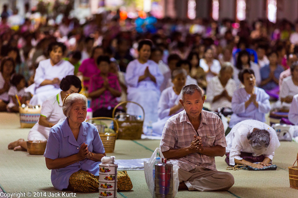 12 JULY 2014 - PHRA PHUTTHABAT, SARABURI, THAILAND: People pray at the chanting service before the Tak Bat Dok Mai at Wat Phra Phutthabat in Saraburi province of Thailand. Wat Phra Phutthabat is famous for the way it marks the beginning of Vassa, the three-month annual retreat observed by Theravada monks and nuns. The temple is highly revered in Thailand because it houses a footstep of the Buddha. On the first day of Vassa (or Buddhist Lent) people come to the temple to &quot;make merit&quot; and present the monks there with dancing lady ginger flowers, which only bloom in the weeks leading up Vassa. They also present monks with candles and wash their feet. During Vassa, monks and nuns remain inside monasteries and temple grounds, devoting their time to intensive meditation and study. Laypeople support the monks by bringing food, candles and other offerings to temples. Laypeople also often observe Vassa by giving up something, such as smoking or eating meat. For this reason, westerners sometimes call Vassa &quot;Buddhist Lent.&quot;<br />     PHOTO BY JACK KURTZ