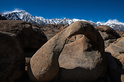 Snowcapped Sierra Nevada mountain range and Mount Whitney behind Mobius Arch, Alabama Hills, California, United States of America