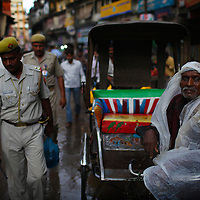 Varanasi, India. A rickshaw driver waits for a fare in between monsoon downpours.