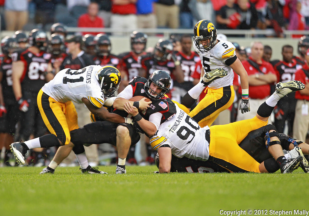 September 01 2012: Northern Illinois Huskies quarterback Jordan Lynch (6) is brought down by Iowa Hawkeyes linebacker Anthony Hitchens (31) and Iowa Hawkeyes defensive lineman Louis Trinca-Pasat (90) during the second half of the NCAA football game between the Iowa Hawkeyes and the Northern Illinois Huskies at Soldiers Field in Chicago, Illinois on Saturday September 1, 2012. Iowa defeated Northern Illinois 18-17.