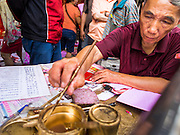 "17 FEBRUARY 2015 - BANGKOK, THAILAND: A calligrapher writes out Chinese New Year's greetings for customers Charoen Krung Road in Chinatown in Bangkok. Chinese New Year is February 19 in 2015. It marks the beginning of the Year of Sheep. The Sheep is the eighth sign in Chinese astrology and the number ""8"" is considered to be a very lucky number. It symbolizes wisdom, fortune and prosperity. Ethnic Chinese make up nearly 15% of the Thai population. Chinese New Year (also called Tet or Lunar New Year) is widely celebrated in Thailand, especially in urban areas like Bangkok, Chiang Mai and Hat Yai that have large Chinese populations.       PHOTO BY JACK KURTZ"