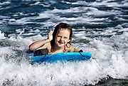 Girl on a wave board enjoying the ride, Ocean City, New Jersey, USA