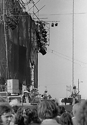 The Grateful Dead Concert at Dillon Stadium on 31 July 1974. B&W Original Film Scan. Band onstage performing with the Wall of Sound in this sidelong view, stage right. Photograph taken with a Nikon FTn Camera with Tri-X film.