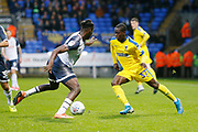 Paul Osew of Wimbledon goes past Josh Emmanuel of Bolton Wanderers  during the EFL Sky Bet League 1 match between Bolton Wanderers and AFC Wimbledon at the University of  Bolton Stadium, Bolton, England on 7 December 2019.