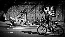 A year anniversary of the Tottenham Riots...A man Cycles past a burnt out vehicle  after the riots in Tottenham which took place last night Saturday August 6, 2011, against the police. Sunday August 7, 2011 Picture by Andrew Parsons/i-Images