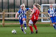 Brighton's Danielle Rowe runs past Kelly Isaac during the FA Women's Premier League match between Brighton Ladies and Cardiff City Ladies at Brighton's Training Ground, Lancing, United Kingdom on 22 March 2015. Photo by Geoff Penn.