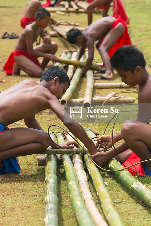 Yapese boys making bamboo canoe, Yap Island, Federated States of Micronesia