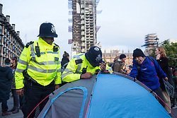 London, UK. 9 October, 2019. Police officers using Section 14 of the Public Order Act 1986 ask climate activists from Extinction Rebellion to remove tents used to block Parliament Square on the third day of International Rebellion protests to demand a government declaration of a climate and ecological emergency, a commitment to halting biodiversity loss and net zero carbon emissions by 2025 and for the government to create and be led by the decisions of a Citizens' Assembly on climate and ecological justice.