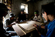 Carrom is one of the most popular games in South Asia and you can find games from Pakistan and North India to Kathmandu. It involves hitting colored game pieces into pockets in a manner similar to billiards, but it's played on a 29-by-29-inch board rather than a full-sized table. Also, you use your fingers rather than a cue stick to flick a striker piece, which is similar to a cue ball. Two to four players compete, divided into two teams in a four-player game, with the winning side determined by sinking nine pieces followed by the red piece, known as the queen. <br /> <br /> In this image, villagers from Nesang in Himachal Pradesh play a game of carrom.