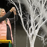 """Junior Auxiliary member Emily Oxford, of Tupelo, hangs decoration onto a tree as she helps prepair for the Junior Auxiliary Charity Ball that will be held Friday night at the BancorpSouth Arena. The theme for the 55th Annual Charity Ball is """"Once Upon a Time in Tupelo""""."""