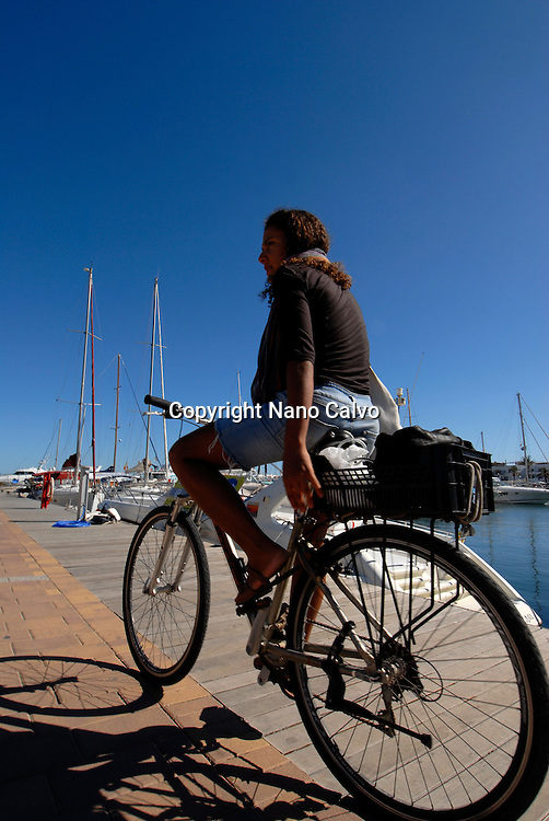 Young brazilian woman in her bike, La Savina, Formentera