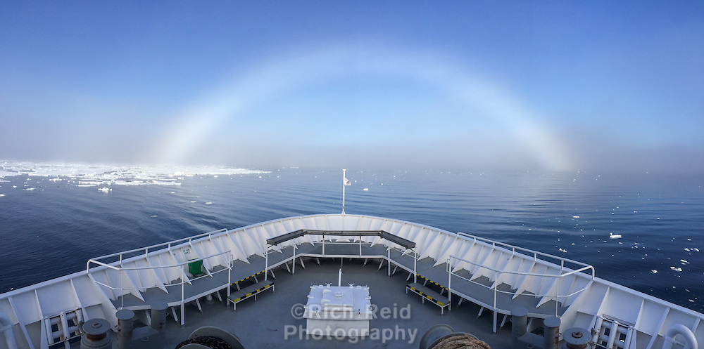 Bow of the ship and fog bow over the sea ice at 80 degrees north in Svalbard, Norway. A weather phenomenon that occurs in dense fog at exteme latitudes.