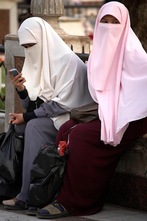 Muslim girls with cellphones at Khan-alKhalili Bazaar in Cairo, Egypt