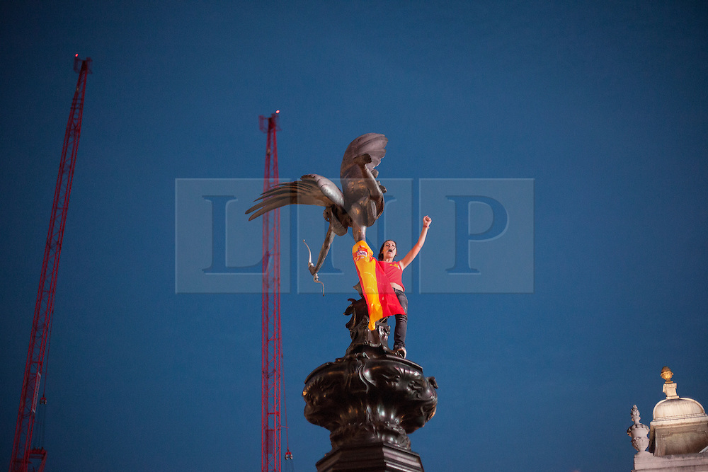 © licensed to London News Pictures. London, UK 01/07/2012. A Spanish football fan climbs to the Eros Statue in Piccadilly Circus, London as their team win the Euro 2012 final in Kiev. Photo credit: Tolga Akmen/LNP