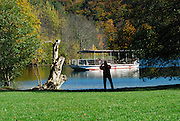 Boat on lake, person taking photograph in silhouette in foreground. Plitvice National Park, Croatia