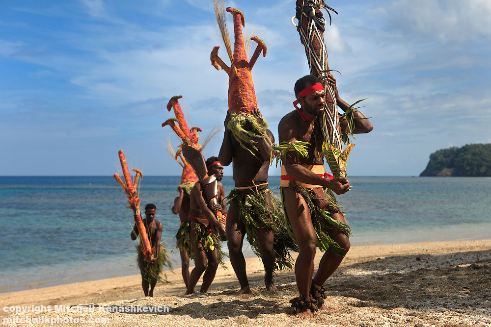 """Traditional Nalawan dancers making their way to the ceremony through """"Fire Beach"""" near the village of Labo, South West Bay, Malekula."""