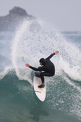 © Licensed to London News Pictures. 22/04/2020. Padstow, UK. A surfer catches a wave at sunrise this morning near Padstow on the north coast of Cornwall. A period of warm weather is set to continue for the rest of the week. Photo credit : Tom Nicholson/LNP