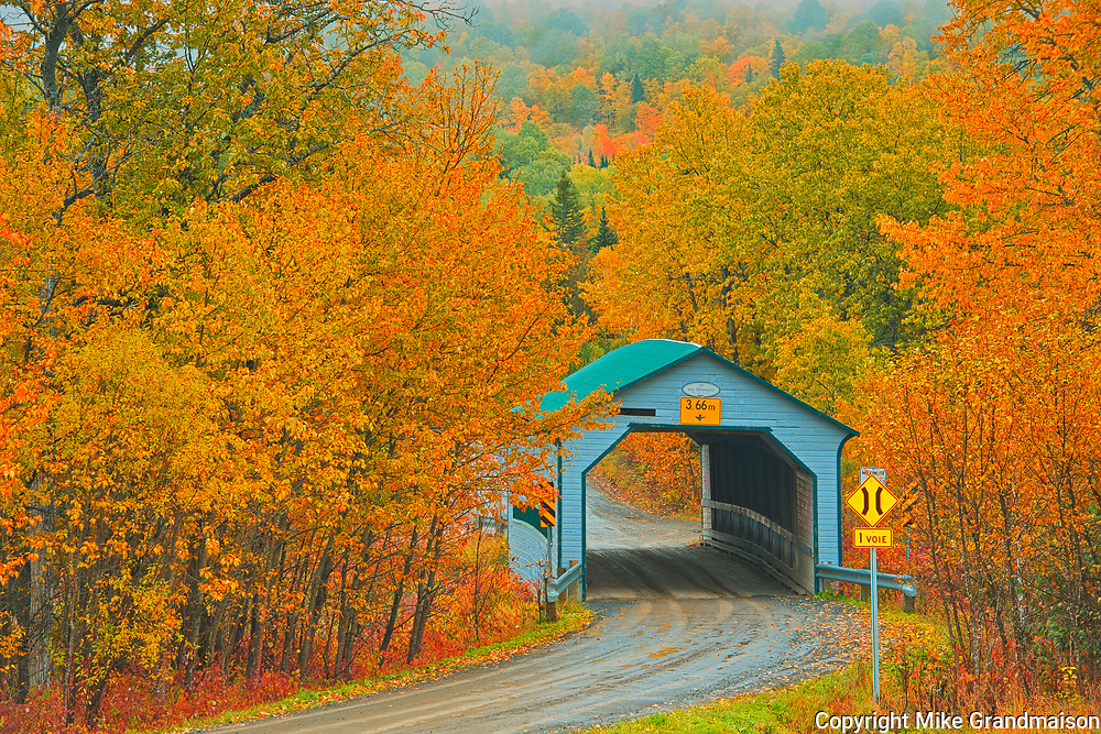 Autumn colors surround the covered bridge - Pont Des Draveurs - across the Petite rivière Neigette.<br />