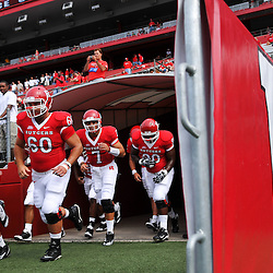 Sep 7, 2009; Piscataway, NJ, USA; Rutgers wide receiver Carl Harris (82) offensive lineman Caleb Ruch (60) quarterback Tom Savage (7) and defensive tackle Michael Larrow (90) run onto the field prior to Rutgers' game against Cincinnati in NCAA college football at Rutgers Stadium.