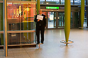 Greeting driver holding passenger name card in Arrivals at Heathrow's Terminal 5.