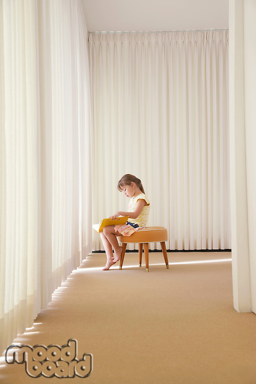 Girl (5-6) sitting on stool in room reading book side view