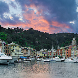 Sunsets over the scenic harbor of Portofino, Italy. Portofino is a hot spot for large private yachts during the summer months.