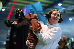 "© Licensed to London News Pictures . 06/12/2015 . Manchester , UK . Princess Leia ( Michelle Seaman , 36 from Surrey) runs for her life with her Wookie daughter ( Elodie Seaman - correct - 16 weeks ) as Darth Vadar ( husband Luke Seaman , 37 ) chases them with his lightsaber extended . Fans attend Star Wars exhibition "" For the Love of the Force "" at Bowlers Exhibition Centre in Manchester . Photo credit : Joel Goodman/LNP"