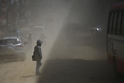 March 22, 2019 - Kathmandu, Nepal - A man crosses the dusty road on the way to Gokarna Forest Resort in Kathmandu, Nepal on Friday, March 22, 2019. (Credit Image: © Skanda Gautam/ZUMA Wire)