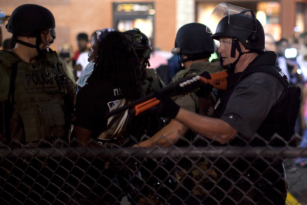 Officers arrest a demonstrator whom they allege threw a water bottle at gathered police. Protests have been ongoing in Ferguson, Missouri since the shooting death of Michael Brown, the eighteen-year-old unarmed teen killed by police on August 9, 2014.