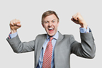 Portrait of young businessman screaming while clenching fist over light gray background