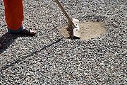 man sweeping stones