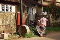 A man carries a basket on his head while walking through the streets of Cochin, India